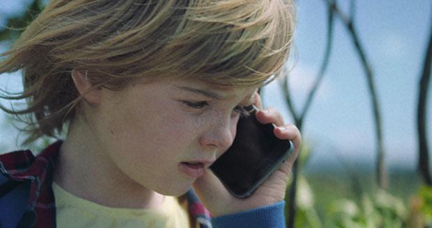 Jongen belt met mobiele telefoon in de natuur.