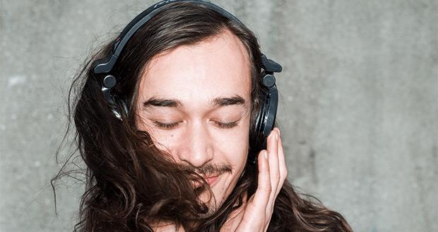 Man luistert muziek via zijn telefoon