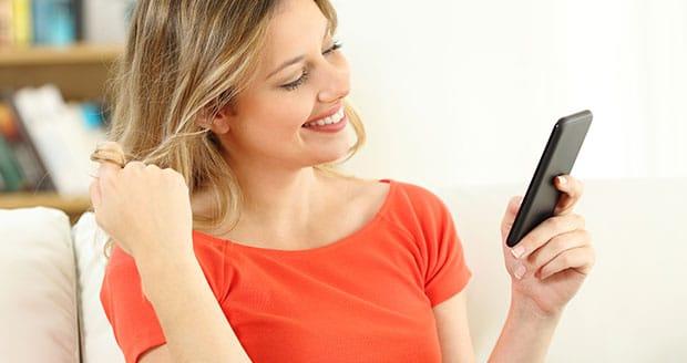 Vrouw lacht naar haar telefoon.