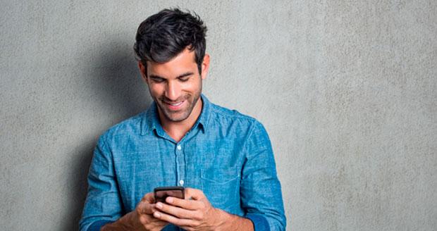 Man kijkt lachend naar zijn telefoon.