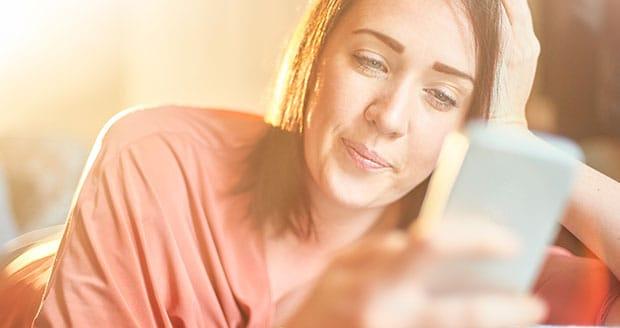Vrouw kijkt op haar telefoon.